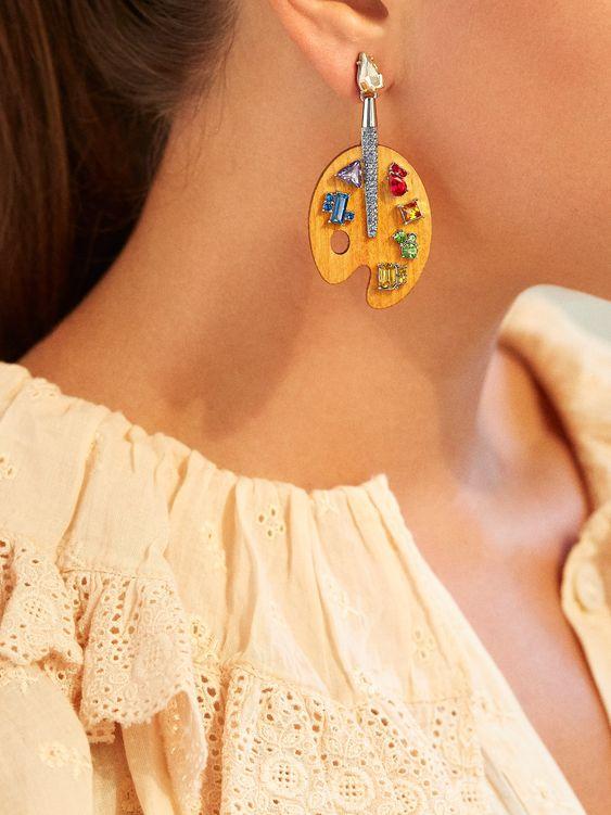 woman wearing painting themed earrings